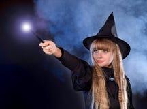 Mädchen im Hut der Hexe mit magischem Stab. Lizenzfreies Stockfoto