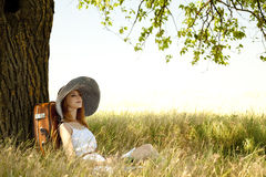 Mädchen im Hut, der nahe Baum an der Landschaft sitzt. Stockbild