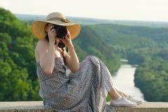 Mädchen im Hut macht Fotos vor dem hintergrund des grünen Waldes und des Flusses Lizenzfreies Stockbild