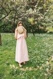 Mädchen im Hut und im Kleid im Garten stockfotos