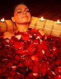 Mädchen im Jacuzzi mit dem rosafarbenen Blumenblatt und Kerze. lizenzfreie stockfotografie