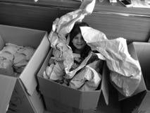 Mädchen im Kasten mit Papier Stockbilder