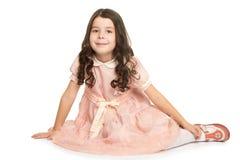 Mädchen im Kleid, das auf dem Boden sitzt Stockbild