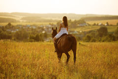 Mädchen im Kleid, das auf einem Pferd sitzt Lizenzfreie Stockfotos
