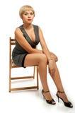 Mädchen im Kleid, das auf einem Stuhl sitzt Stockbilder