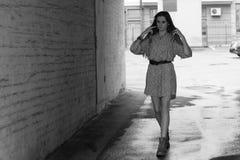 Mädchen im Kleid und in den Stiefeln geht auf die Stadt Lizenzfreies Stockfoto