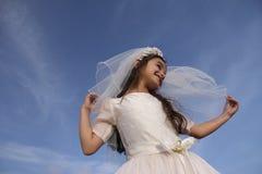 Mädchen im Kleid und im Schleier der heiligen Kommunion Lizenzfreies Stockfoto
