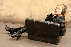 Mädchen im Koffer hörend Musik lizenzfreie stockbilder