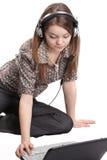 Mädchen im Kopfhörer mit Notizbuch lizenzfreie stockbilder