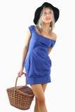 Mädchen im kurzen blauen Kleid und im Hut, einen Weidenkorb halten. Stockbilder