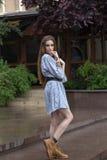 Mädchen im kurzen Kleid und Stiefel in der Stadt Lizenzfreies Stockfoto