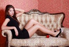 Mädchen im kurzen schwarzen Kleid auf Weinlesecouch Stockfotografie