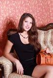 Mädchen im kurzen schwarzen Kleid mit Handtasche Stockbild