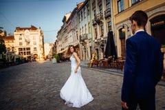 Mädchen im langen Hochzeitskleid schaut auf Kerl über ihrer Schulter Lizenzfreie Stockfotos