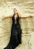 Mädchen im langen schwarzen Kleid, das in den Sanddünen aufwirft stockbild