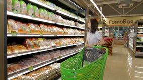 Mädchen im Mall mit Marktlaufkatze voll von Produkten stock footage