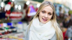 Mädchen im Mantel, der an Weihnachtsmarkt aufwirft Stockfotos