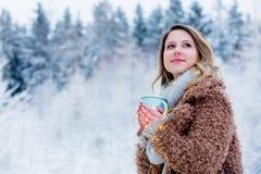 Mädchen im Mantel mit Schale des Getränks in einem Schneewald lizenzfreie stockbilder