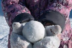 Mädchen im Mantel und in Handschuhen, die einen Schneeball in Form eines Balls halten Lizenzfreie Stockfotografie