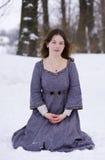 Mädchen im mittelalterlichen Kleid, das im Schnee sitzt Stockfotos