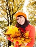 Mädchen im orange Hut des Herbstes, Blattgruppe nahe Baum.