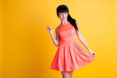 Mädchen im orange Kleid auf einem gelben Hintergrund Stockbilder