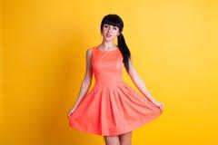Mädchen im orange Kleid auf einem gelben Hintergrund Lizenzfreies Stockbild
