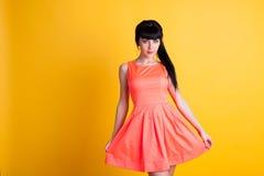 Mädchen im orange Kleid auf einem gelben Hintergrund Stockfotos