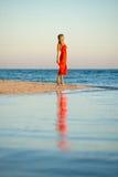 Mädchen im orange Kleid durch Seerand Stockbild