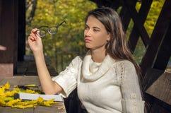 Mädchen im Park, der auf einer Bank hält Gläser in den Händen sitzt Lizenzfreie Stockbilder