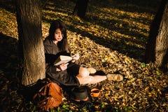 Mädchen im Park las das Buch Stockbild