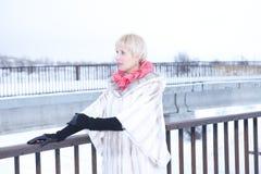 Mädchen im Pelzmantel wirft Mädchen auf Schnee auf Stockbilder