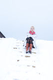 Mädchen im Pelzmantel wirft Mädchen auf Schnee auf Stockfotografie
