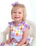 Mädchen im Polka-Punkt-Kleid auf Stuhl Lizenzfreie Stockfotografie