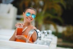 Mädchen im Pool mit einem Glas des roten Cocktails Lizenzfreie Stockfotografie
