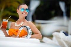 Mädchen im Pool mit einem Glas des roten Cocktails Stockbild