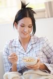 Mädchen im Pyjama, der Getreide isst Stockfoto
