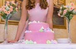 Mädchen im rosa Kleid mit festlichem rosa Kuchen, 2 Blumensträuße von Blumen Lizenzfreies Stockbild