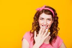Mädchen im rosa pinup-ähnlichen Kleid isst Creme leckt Finger stockfotografie