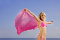 Mädchen im rosafarbenen Badeanzug auf dem Strand Stockfoto