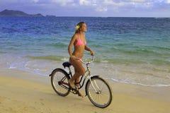 Mädchen im rosafarbenen Bikinireiten ihr Fahrrad Lizenzfreies Stockfoto