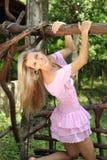 Mädchen im rosafarbenen Kleid auf dem Schwingen Lizenzfreie Stockbilder