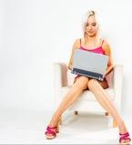 Mädchen im rosafarbenen Kleid mit Laptop Stockbilder
