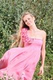 Mädchen im rosafarbenen Kleid mit Rosen Lizenzfreie Stockbilder