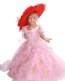 Mädchen im rosafarbenen Kleid und im roten Hut Stockfoto