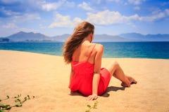 Mädchen im Rot mit nackter Rückseite sitzt auf Sandblicken in Meer Lizenzfreie Stockbilder