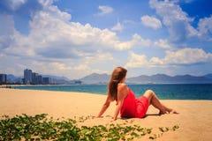 Mädchen im Rot sitzt auf Sandblicken in Meer auf Vordergrundkriechpflanzen Stockfotos