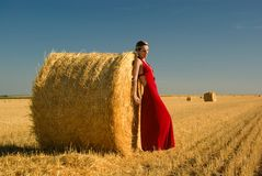 Mädchen im roten Abendkleid, das auf Strohballen sich lehnt. stockfotos