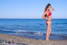 Mädchen im roten Badeanzug am Strand Lizenzfreie Stockbilder