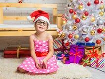 Mädchen im roten Hut und in den lustigen runden Gläsern auf einer Wolldecke in einer Weihnachtseinstellung Lizenzfreie Stockbilder